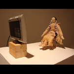 traditional plains First Nations doll seated in a chair in front of a TV monitor