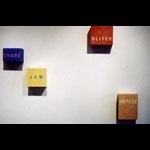 Installation detail 4 colour text paintings on cubes, left to right words 'chaos', 'jam', 'glitch', 'impede'